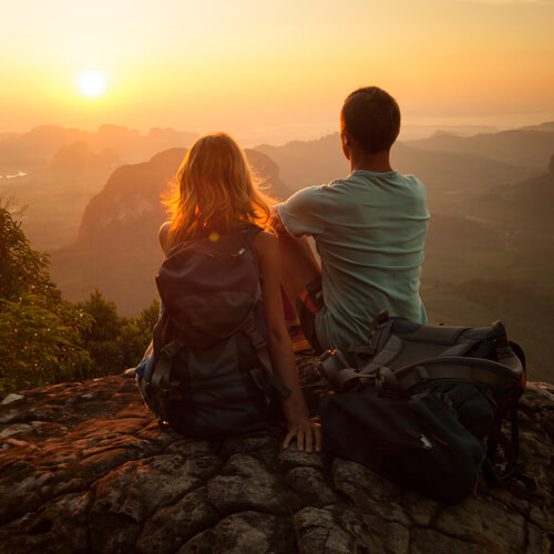 Couple of hikers sitting on top of the mountain and enjoyoing sunrise over valley